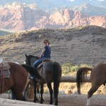 Amy on horseback with the Red Rock Canyon providing a dramatic background.